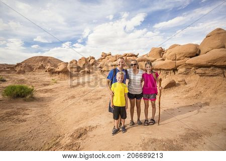 Family hiking together among desert red rock formations at Goblin Valley State Park