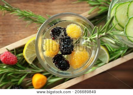 Glass with fresh rosemary drink in wooden case