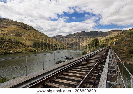Train tracks along the Douro River in the wine region of the Douro Valley in Portugal; Concept for travel in Portugal and in the Douro Region