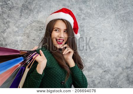 Shopping beautiful girl with paper bags luxury and christmas hat for xmas season and discount lowest price.
