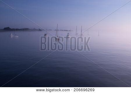 Morning fog in Salem harbor Massachusetts sailboats