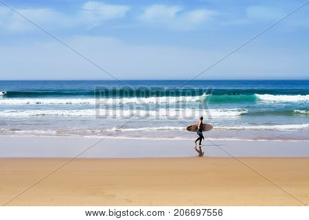Surfer walking on sunny beach with surf board ocean wave run - nice panoramic view of the horizon