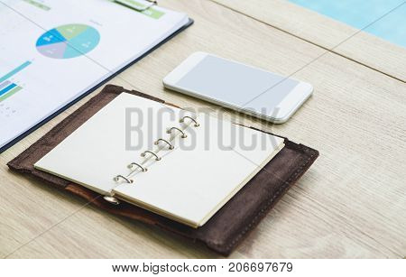 Open blank organizer book with mobile phone and business chart on wood table at office