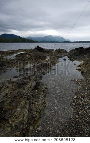 A rocky shore at low tide with tide pools reflecting the gray clouds on a rainy day. across the choppy bay are mountains shrouded in rain clouds.
