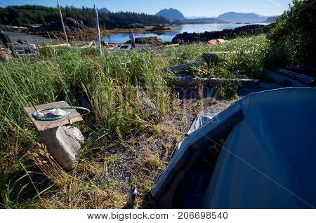 A morning shot of tents beach grass and kayaks on Spring IslandBC with mountains in the distance.