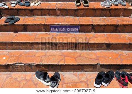 Ayudhaya Thailand - 14 September 2017 - The Take Off Shoes sign posts on the steps in front of the entrance to a famous temple Wat Yai Chai Mongkol in Ayudhaya Thailand on September 14 2017.