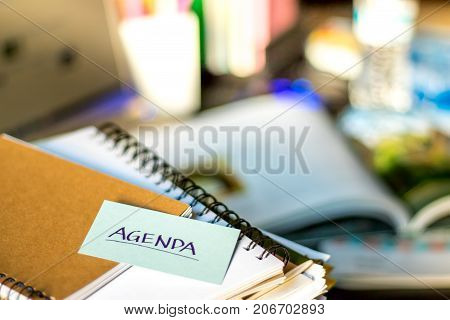 Agenda; Stack Of Documents And Laptop At Working Desk.
