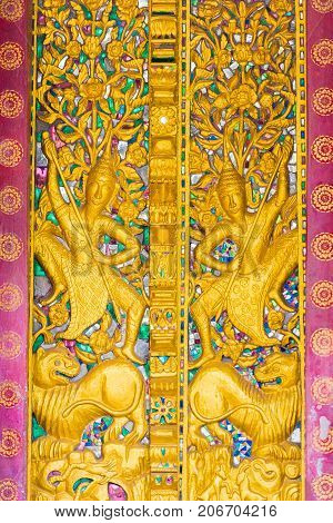 Bas-relief On The Wall Of The Temple Wat Sensoukaram In Louangphabang, Laos. Vertical. Close-up.