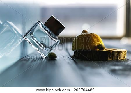 Small bottle for perfumery a lemon and almonds on a light background.
