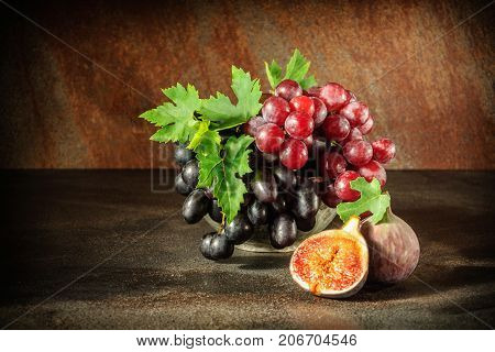 Still life with fruits: grape fig in the antique copper tin cup.