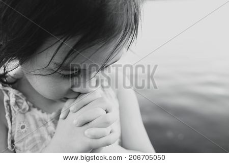 little multiethnic girl praying kid child pray conceptmono toning shallow DOF