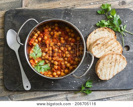 Tomato sauce braised chickpeas in a pot and grilled bread. Delicious vegetarian lunch on a rustic wooden background top view