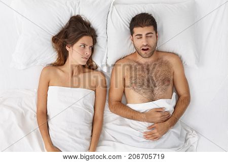 Top View Of Angry Young Female Having Mad Expression Feeling Disturbed With Snoring Husband, Wishing