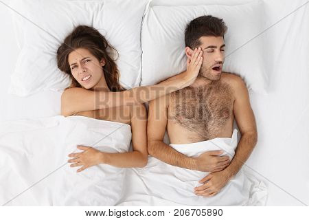 Health And Snoring Concept. Stressful Brunette Female Pushes Away Snore Husband Who Distrubes To Hav
