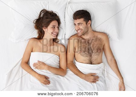 Happy To Be Together. Indoor Portrait Of Joyful Young Male And Female Lying In Bed Covered With Whit