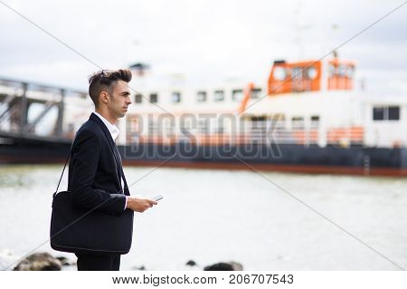 Ambitious young entrepreneur thinking of logistics and standing on dock. Pensive handsome businessman contemplating seascape. Business in cargo shipping concept