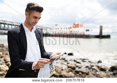 Concentrated young broker analyzing newspaper articles while walking on shore of big city. Modern enterprising businessman working everywhere. Last news concept