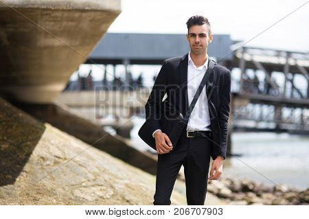 Confident handsome student walking over shore after classes and looking at camera. Smiling young man with briefcase on stroll. Modern businessman concept