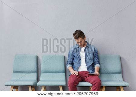 Handsome Man In Denim Jacket And Fashionable Trousers Sits In Queue, Waits For Long Time His Turn, F