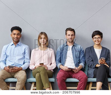 Technology, Ethnicity And People Concept. International Group Of Young Women And Men Sit In Queue Li