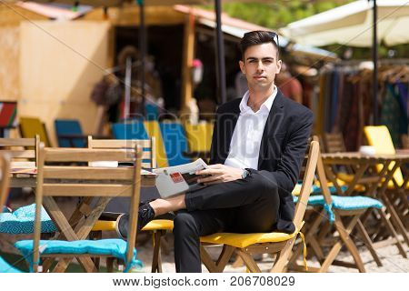 Handsome businessman starting his day with newspaper in outside cafe and looking at camera. Serious confident young manager in suit sitting at table. Business lifestyle concept