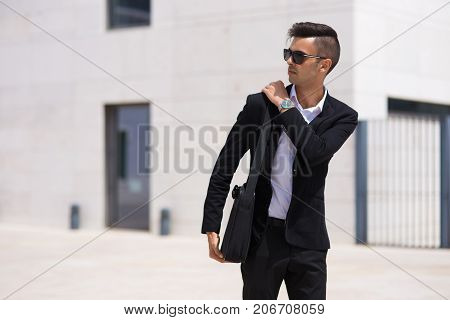 Handsome young manager leaving office and adjusting handle of briefcase on shoulder. Serious confident businessman looking away and walking over financial district. Rich man concept