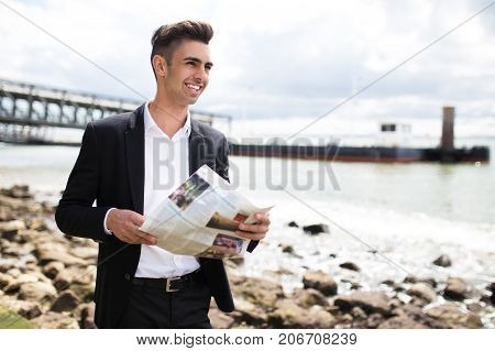 Happy purposeful businessman reading newspaper and enjoying stroll on shore. Cheerful handsome young man looking into distance and contemplating landscape. Ambition concept