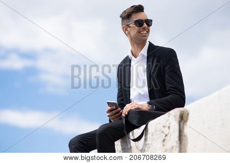 Happy young man in suit enjoying stroll and looking away. Positive handsome businessman with smartphone relaxing outdoors and having good time. Cool guy concept
