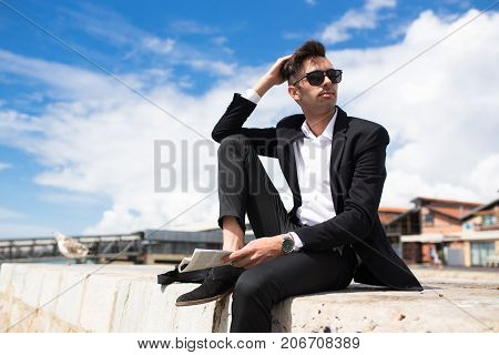 Pensive handsome businessman dreaming of future and looking away. Serious fashionable young man in suit holding newspaper and resting alone. Aspirations concept