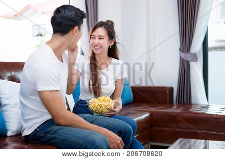 Young Asian couple in sweet moment relax laughting and eating popcorn to watching television in living room.