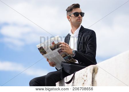 Purposeful handsome businessman with newspaper looking away while sitting on edge of concrete slab. Serious young man interested in last news. Stroll concept