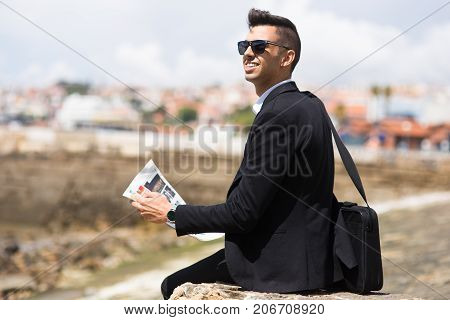 Thoughtful businessman dreaming of big goals or planning his route in foreign city. Cheerful motivated male manager reading news outdoors. Work and travel concept