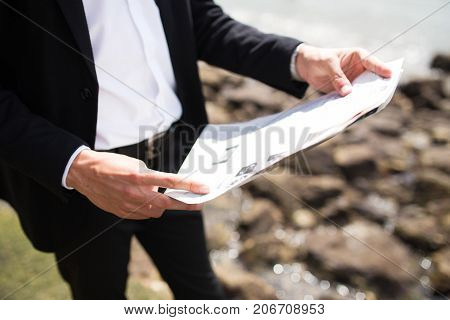 Unrecognizable businessman using pocket map and finding location. Or man looking through news in newspaper outdoors. Publication concept