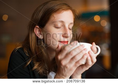 Close-up of face of young Caucasian woman holding cup on hands enjoying smell of coffee at cafe. Drink and leisure concept