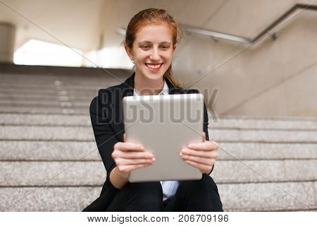 Portrait of happy young Caucasian businesswoman or student sitting on stairs, using touchpad and smiling. Modern technology concept