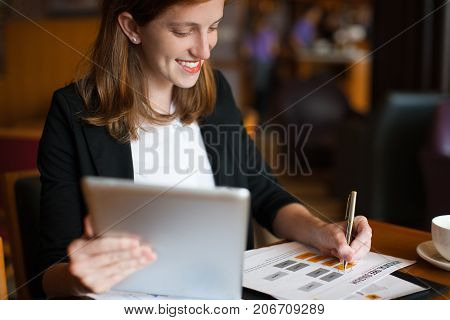 Portrait of happy young Caucasian businesswoman sitting at table, holding touchpad and making notes in paper at cafe. Work life balance concept