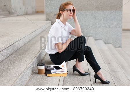 Portrait of pensive young Caucasian businesswoman wearing glasses sitting on staircase with papers, calculator and coffee cup. Work life balance concept