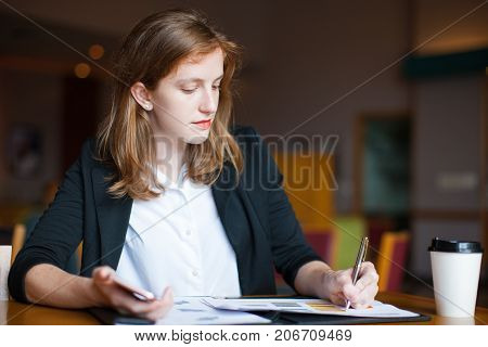Portrait of serious young Caucasian businesswoman sitting at table and making notes on document at cafe. Work life balance concept