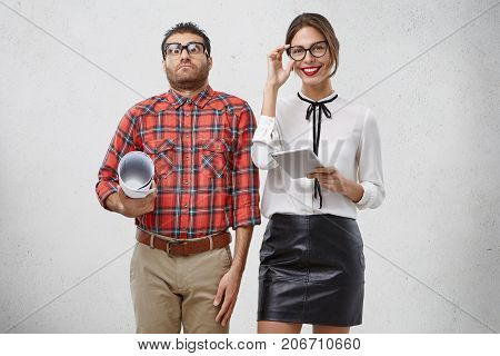 Funny Clumsy Student In Checkered Shirt And Glasses Stands Near His Young Teacher Who Teaches Him, H