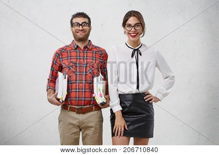 Clever Male Swot In Old Fashionable Glasses And Checkered Shirt Holds Many Books Under Arms, Has Fun