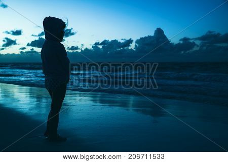 Silhouette Of A Little Girl Staring At The Ocean