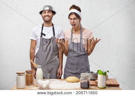 Furious Irritated Woman Wears Apron, Gestures In Anger As Has Quarrel With Husband At Kitchen, Repro