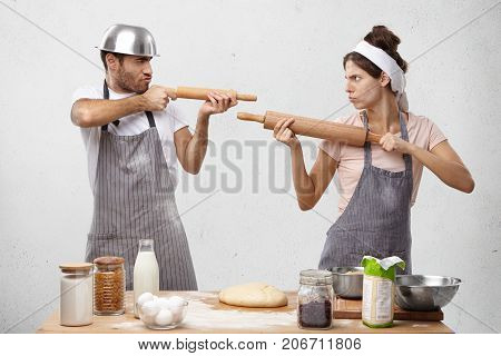 Serious Cook Competitors Pretend That Rolling Pin Is Gun, Look At Each Other As On Shooting Mark, Tr