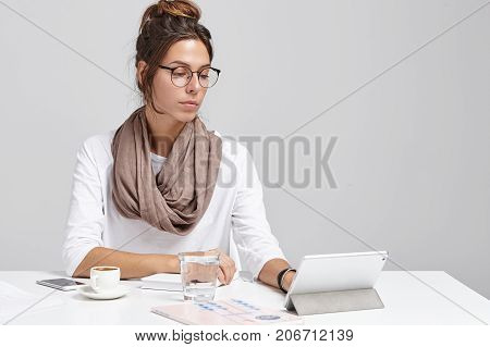 Businesswoman In Office Works On Digital Tablet, Look Seriously. Young Clever Pretty Woman Uses Elec