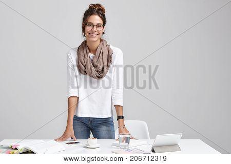 Portrait Of Positive Female Student Prepares For Classes, Reads Scientific Literature, Uses Modern T