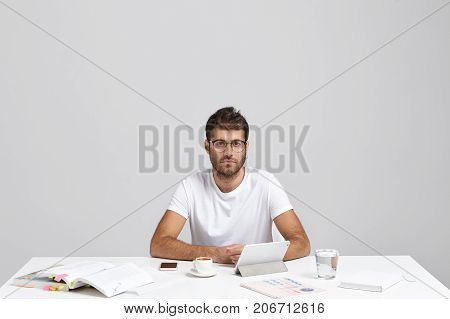 Convinced Caucasian Man With Stubble And Trendy Hairstyle, Wears Casual T Shirt, Sits At White Table