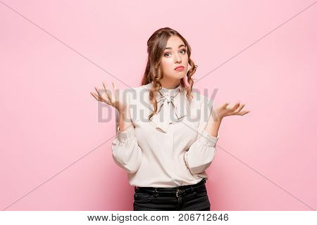 Business woman remembers or thought. office manager. studio photo on a pink background