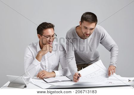 Two Successful Professional Male Constructors Studying Blueprints At Spacious Light Office, Having L