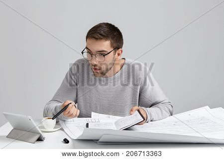 Young Male Designer Stares In Screen Of Tablet, Has Deadline To Finish Drawing Sketches, Being Busy