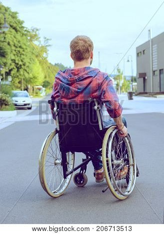 Disabled Man In Wheelchair On Road